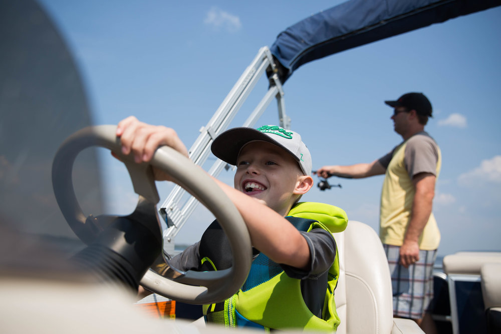boy driving boat while dad fishes