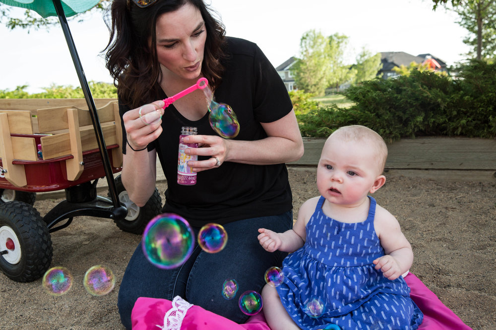 Mom blowing bubbles for baby at beach