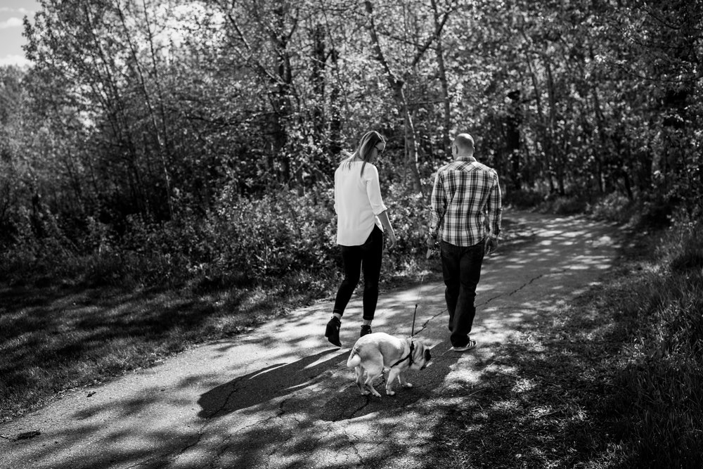 couple walking in the woods with dog