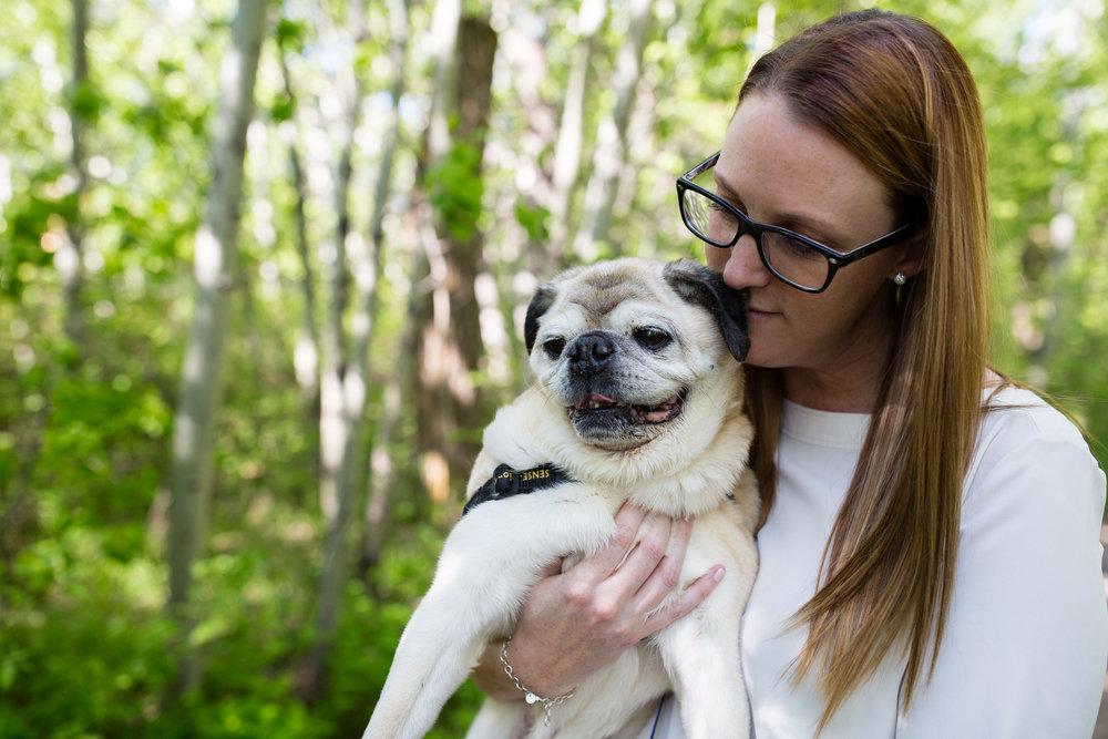 woman cuddling pug dog