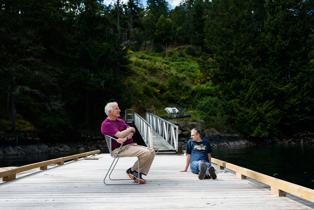 Father and adult son sitting on a dock