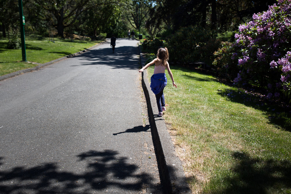 young girl walking sidewalk balance beam