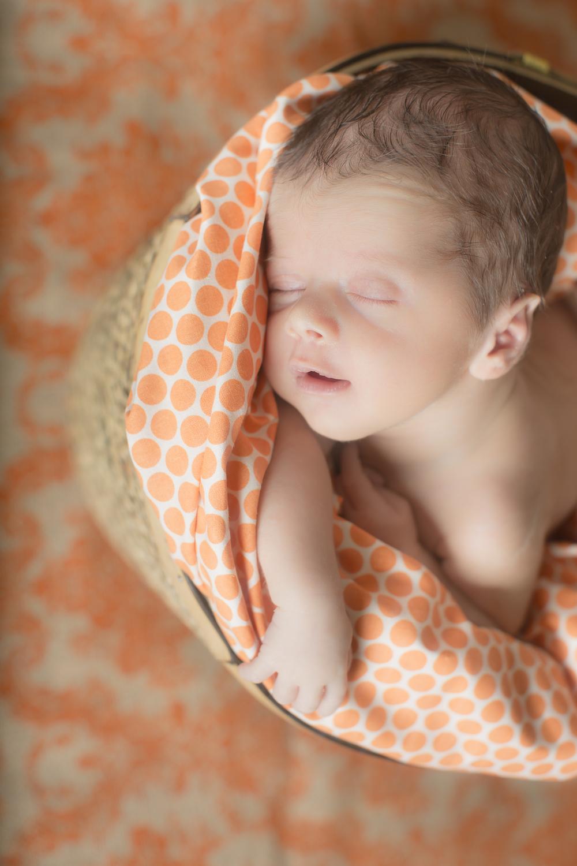 15 orange polka dot modern newborn boy photography in straw basket with burlap background studio session.jpg