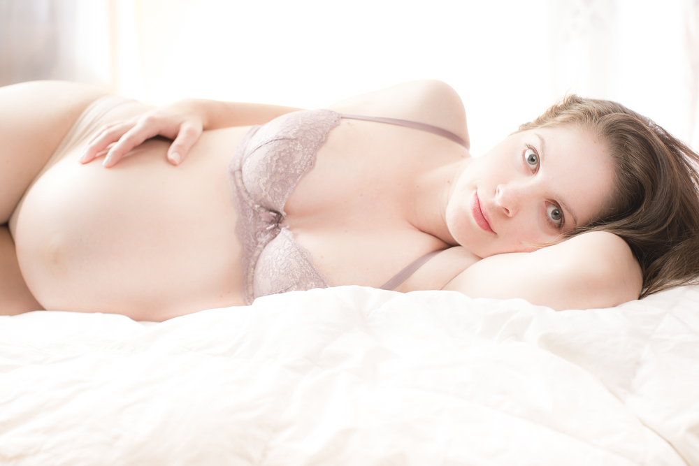 18 modern sexy maternity photography session momma staring eyes laying down lingerie.jpg