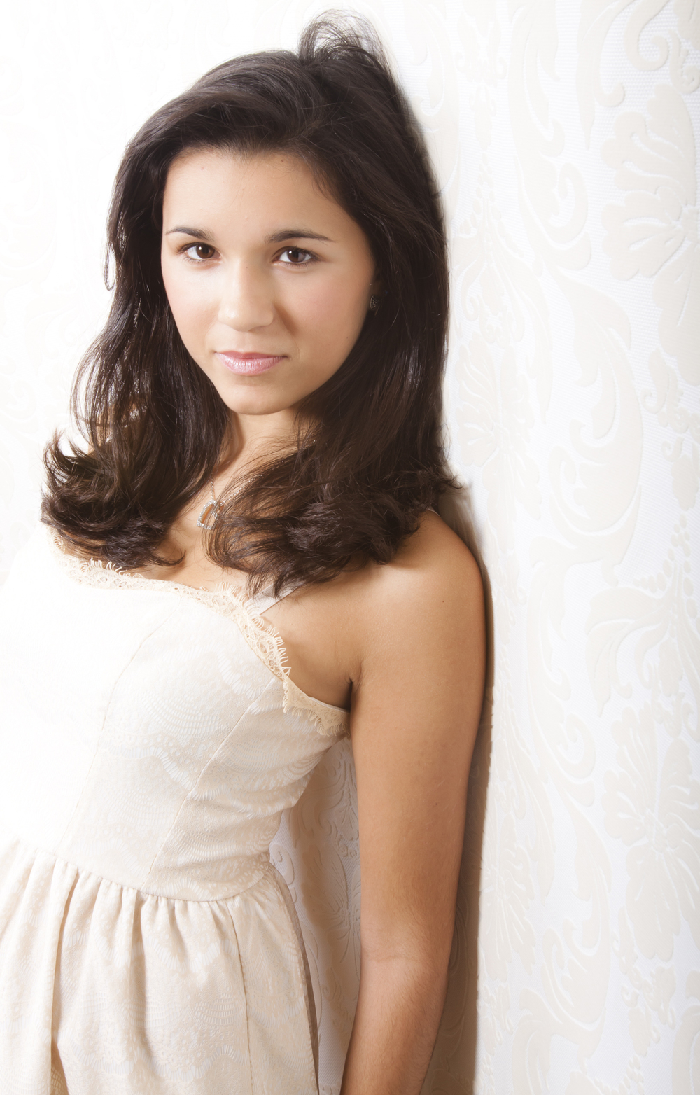 06 modern styled senior portrait sessions in white lace dress leaning on wall 8546.jpg