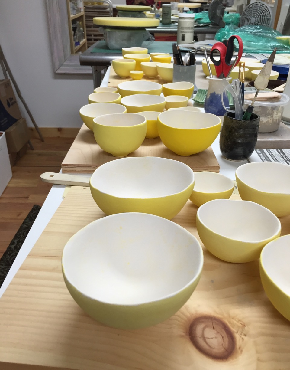 Bowls being glazed. Each group is glazed in different shades of yellow.