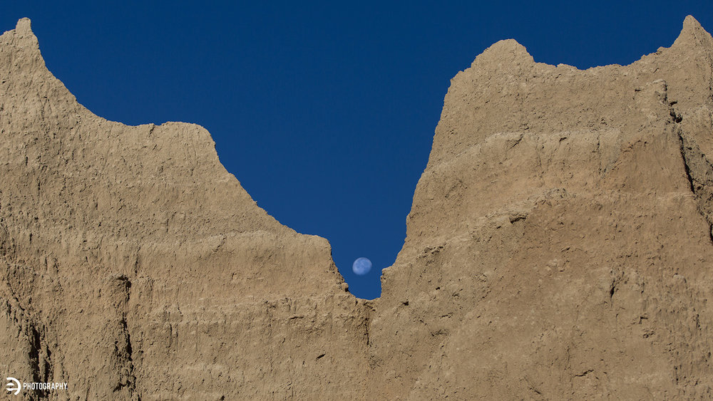 The early-morning moon peaked through the towering rock.