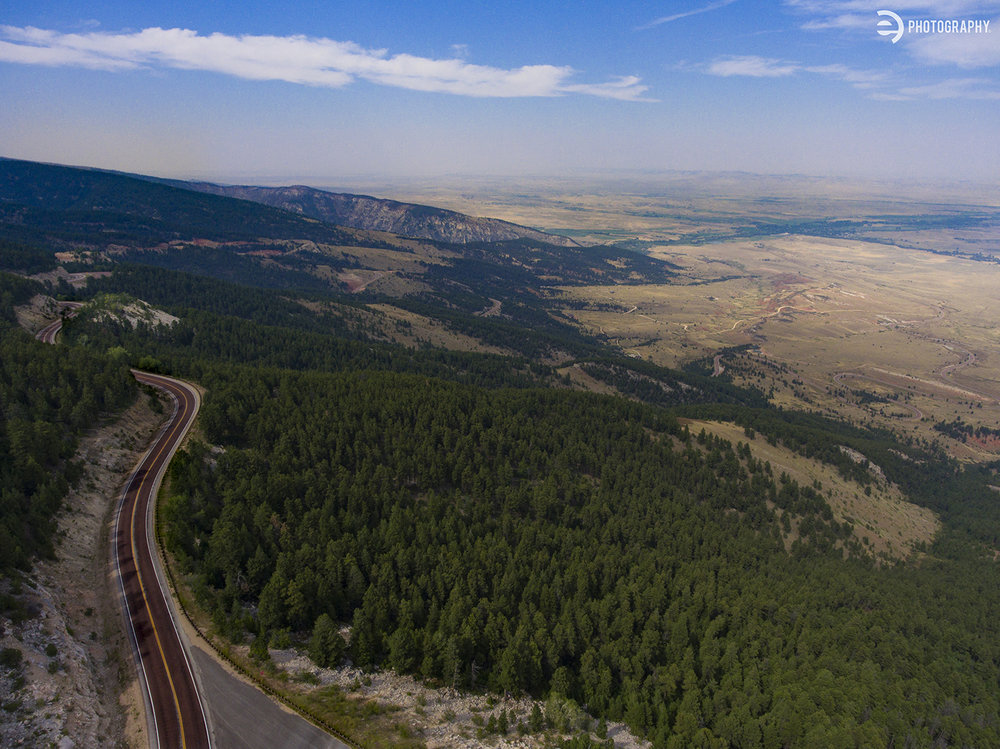 If you take the northern pass (Hwy 14) through the Bighorn National Forest near Dayton, WY - the road winds back and forth, climbing up the mountain at a rapid pace. We stopped near the top to check out the view and watch some nice young man jump off a perfectly good mountain with a sail strapped to his back. This view provided by the aerial drone at high altitude.