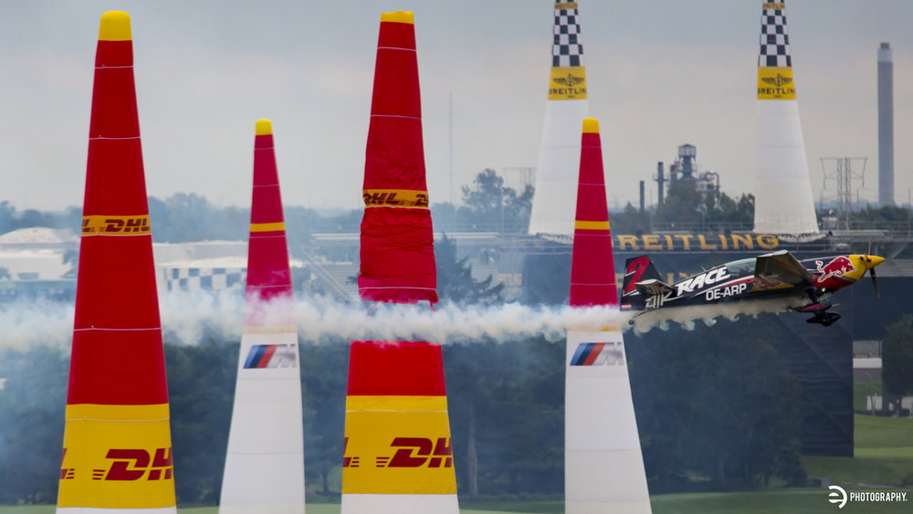 The tip of a pylon is ripped from the base as a Red Bull plane flies through.