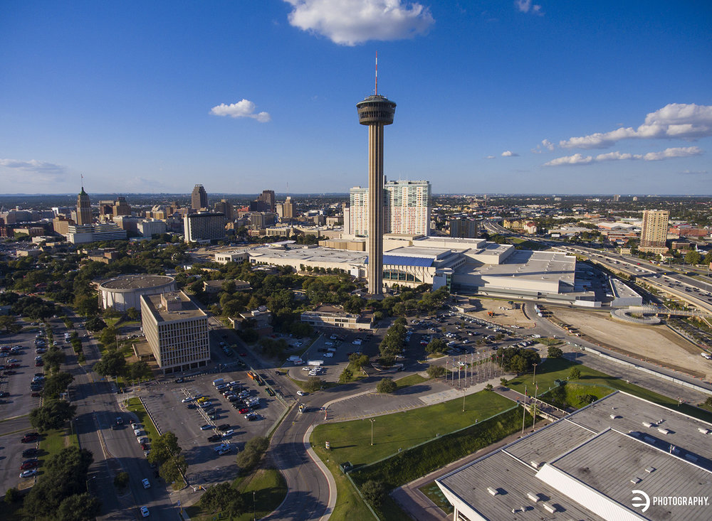 The Tower of the Americas in the foreground of an aerial drone photo of downtown San Antonio.