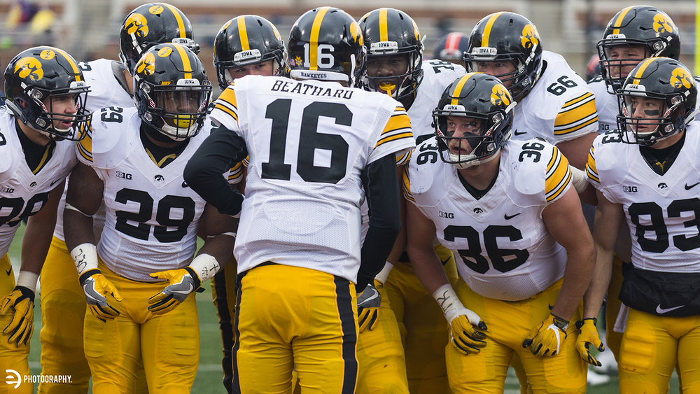 The team listens intently as quarterback CJ Beathard provides direction.