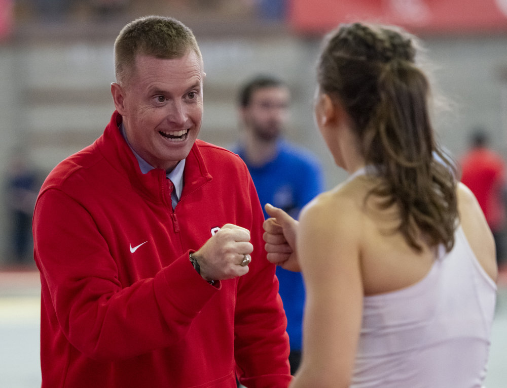 Head coach Artie Smith offers a fist-bump to a student-athlete after a solid showing in the hurdles.