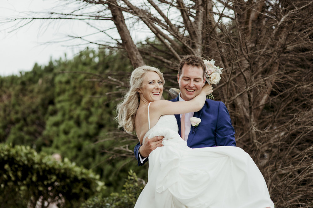 Groom carrying bride at Mudbrick wedding