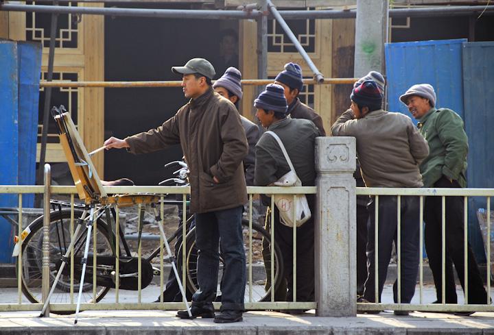 Migrant workers admiring artists work in the park in Beijing