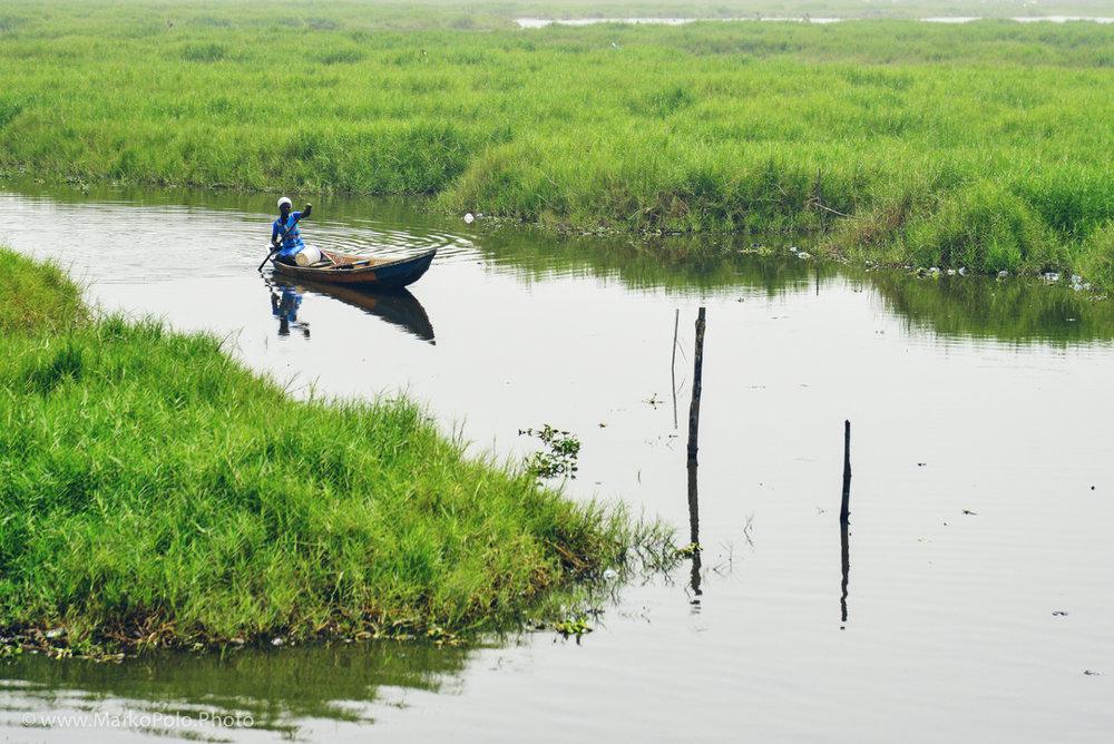 Benin (1) - Woman paddles her boat near village of Ganvie