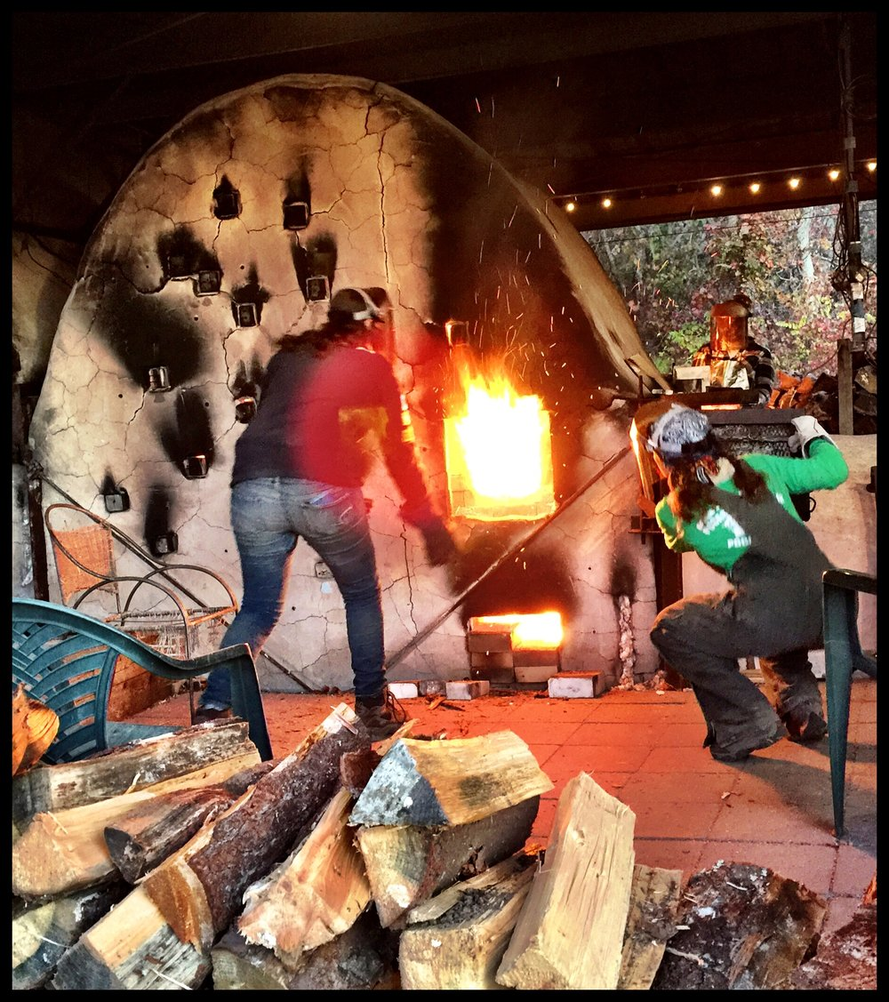 Artists work together to stoke the 2nd chamber by tossing wood into the firebox. Photo credit: Hollis Engley