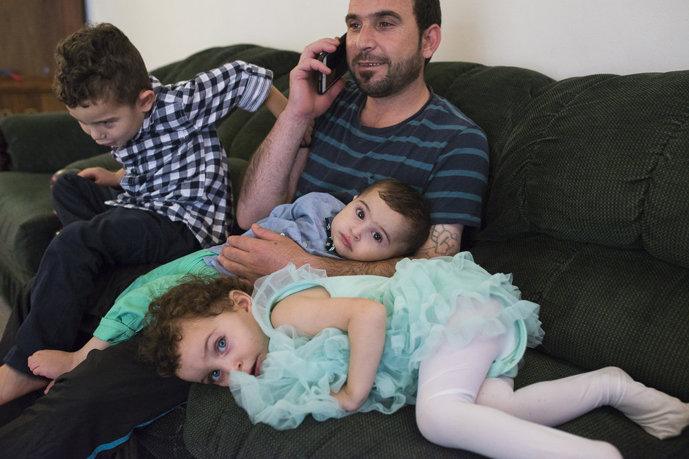 He calls and check with his family who are in Jordan as the children play around him.