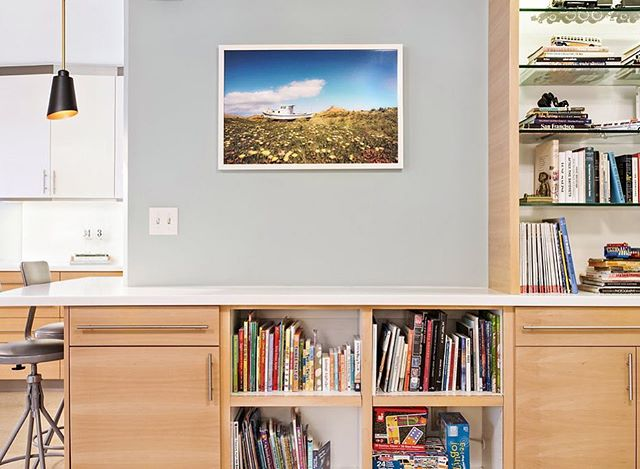 Custom Beech Kitchen cabinetry wraps around into the living room for a full wall of book and toy storage. A combination of open and covered storage is great for families with little ones — hide the stuff that needs to be hidden and provide easy access for frequently used books and toys. The built-in lighting feature in the bookshelf area provides a nice and mellow lighting option in those early morning hours when it's just too early for overhead lighting. 📷: @caterphotography  #builtbyhand #ableandbaker #letsbuild #beech #wood #veneer #custom #kitchendesign #books #bookshelves #customfurniture #madeincalifornia #madeinla #lighting #moderndesign #renovation #moderninteriors #booksofinsta