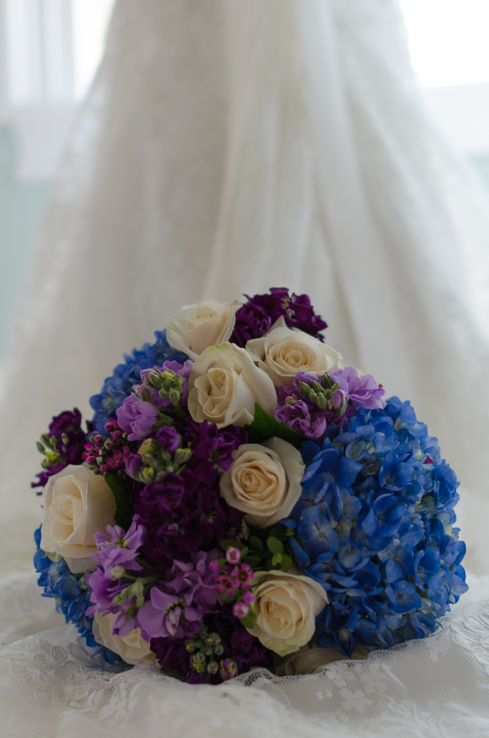 Not a fan of the typical red, Kimi chose beautiful white roses with blue hydrangea.