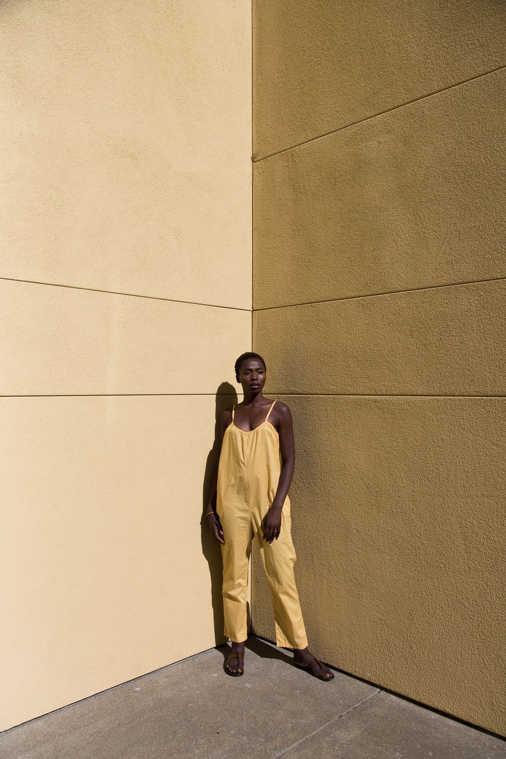 Hawa wears a Sol jumpsuit in gold.