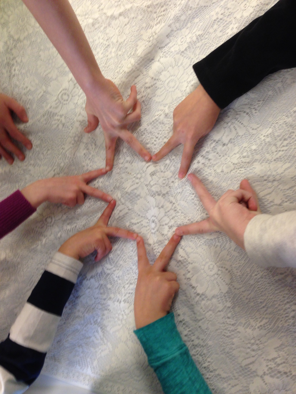 Students from the United Parish of Lunenburg make a Star of David with their hands.