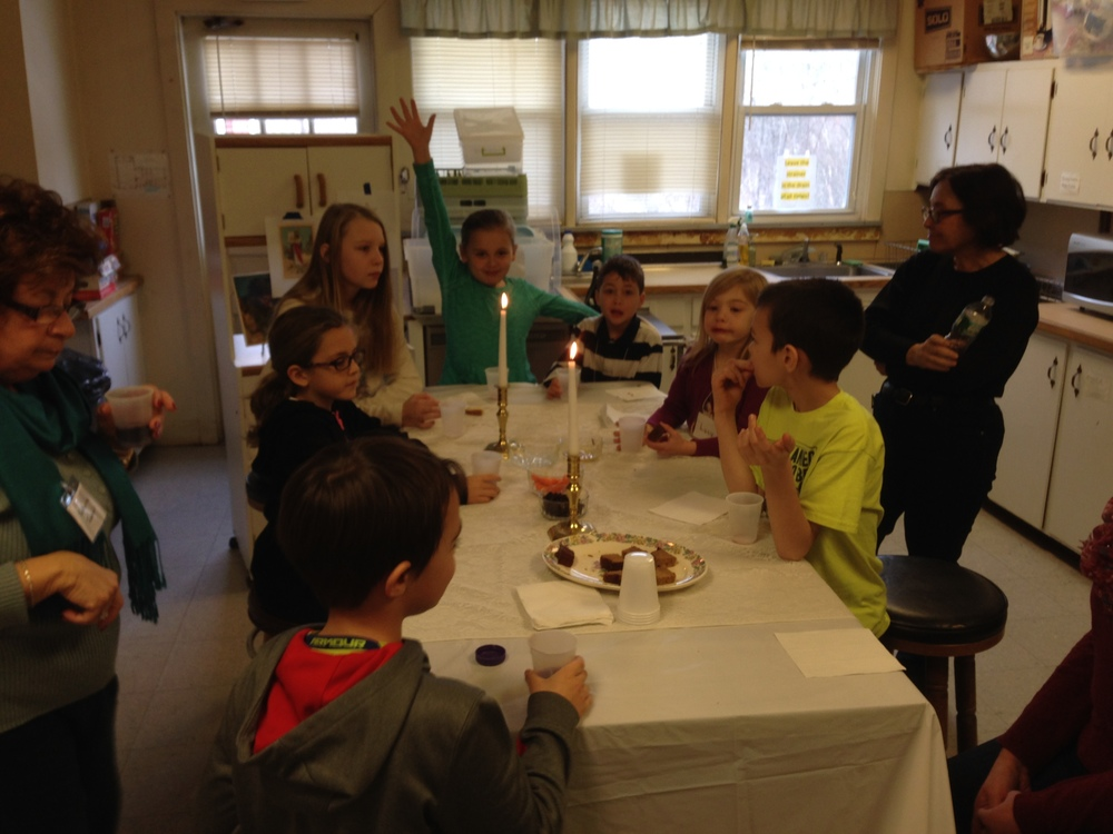Middle-school students at a Shabbat table.