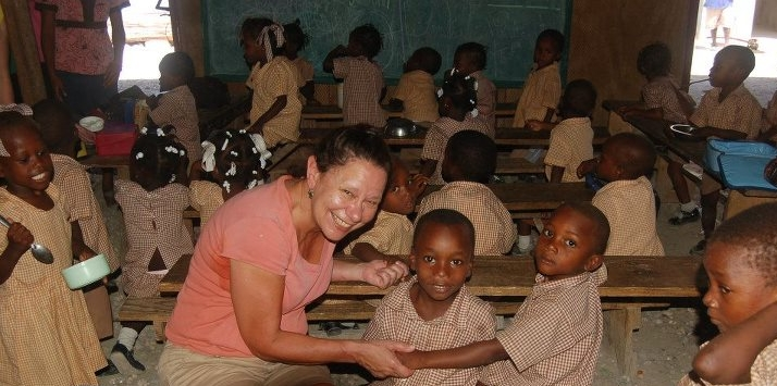 The Rev. Debra Pallatto-Fontaine laughs with a group of students at Be Like Brit Orphanage in Grand Goave, Haiti.