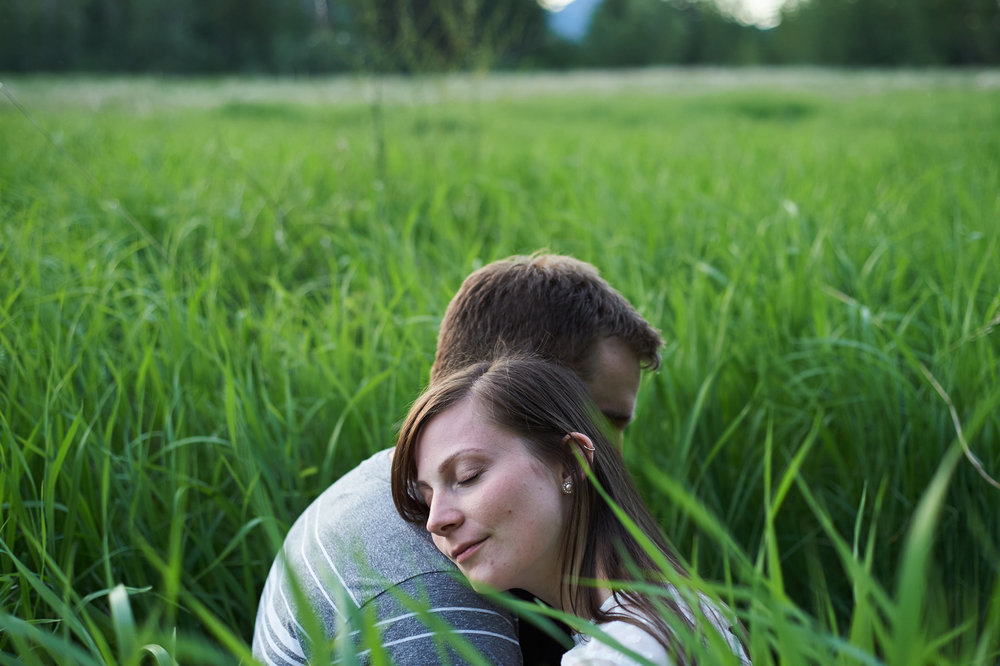 engaged-couple-in-a-grassy-field-hugging.jpg