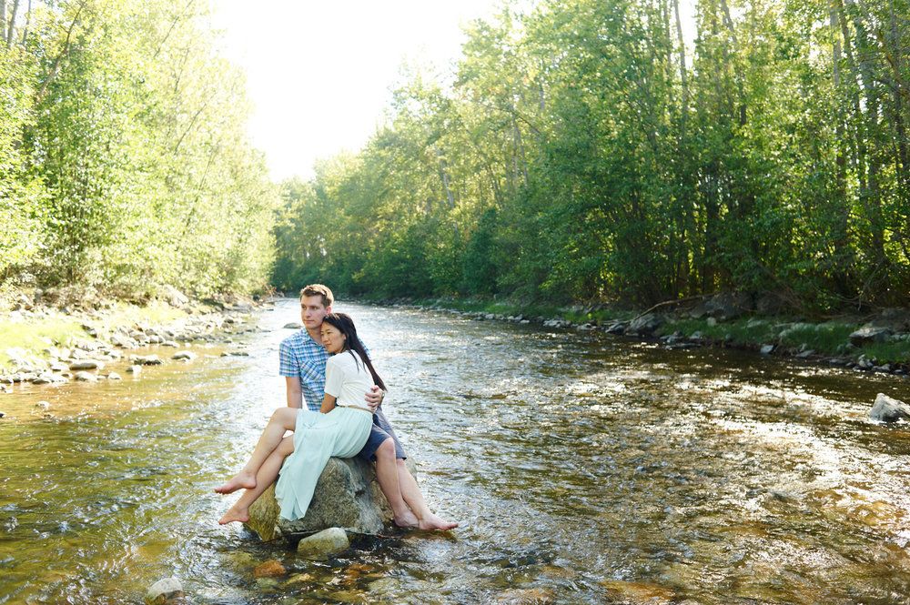 engaged-couple-sitting-on-a-rock-in-mission-creek-park-in-the-sun.jpg