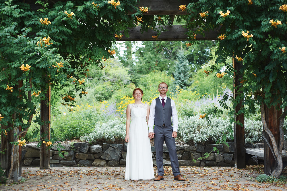 bride-and-groom-standing-hand-in-hand-under-a-wooden-trellis.jpg