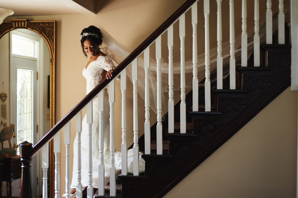 bride-walking-down-the-stairs-veil-trailing.jpg