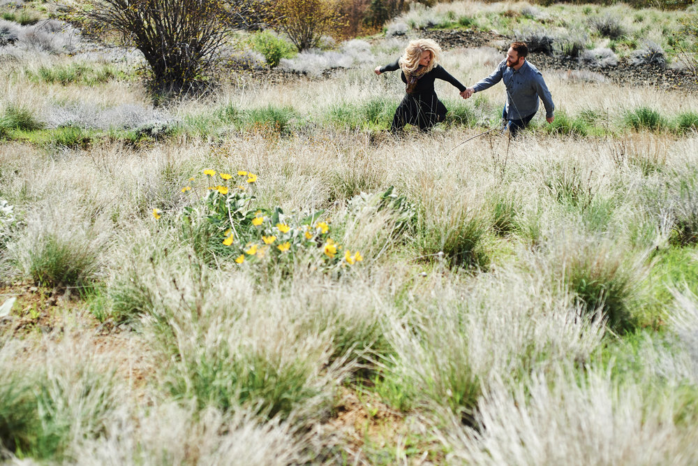 engaged-couple-running-through-a-flower-meadow.jpg