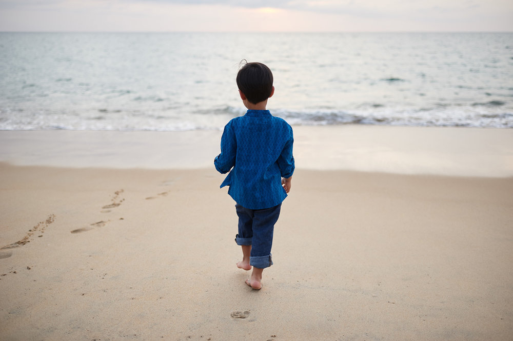 boy-walking-on-sandy-beach-in-thailand-family-session.jpg