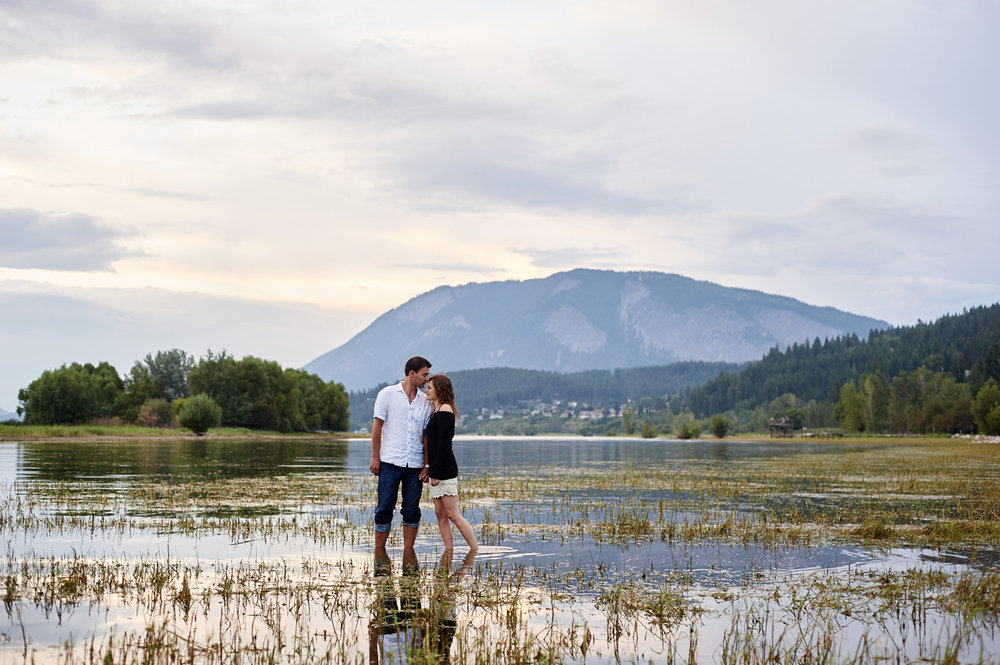 engaged-couple-standing-in-water-in-evening-light-kamloops.jpg