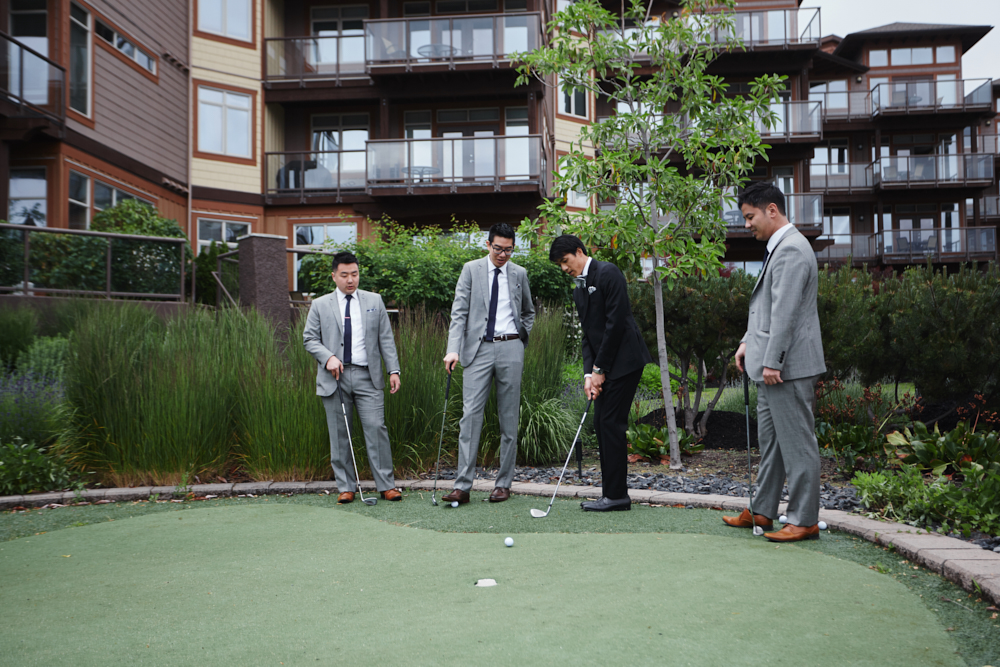 groom and groomsmen playing mini golf