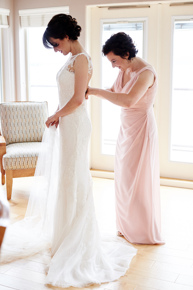 bridesmaid doing up brides wedding dress