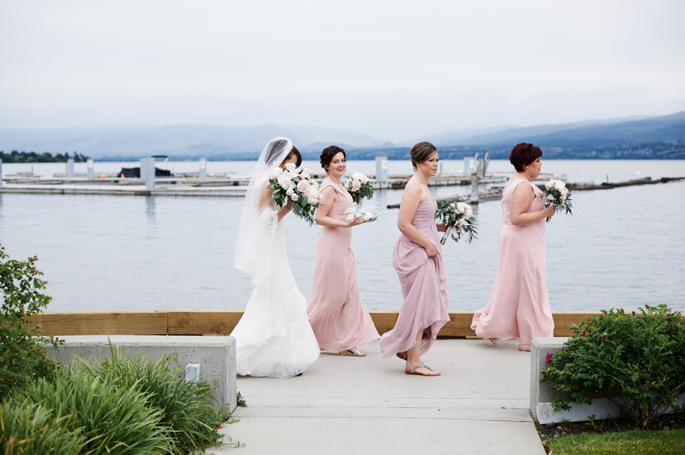 bride and bridesmaids walking beside Okanagan lake