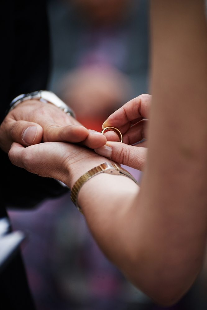 bride puts wedding ring on grooms finger