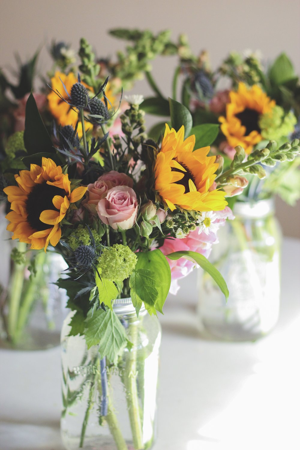 Sunflowers blue thistle and pink roses mason jar flower arrangement – Roots and Wildflowers