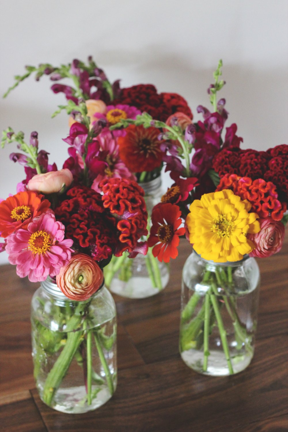 Red orange and yellow zinnia and celosia mason jar flower arrangement – Roots and Wildflowers