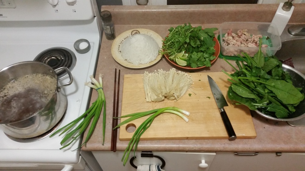Reheat the broth, boil some rice noodles, pick the chicken off the bones, wash some greens and you're about to have yourself a great time. This is just one option of what can be done with a good home made soup broth.  Pictured: enoki mushrooms, spinach, mint, watercress, cilantro, green onions, lime wedges and rice noodles.