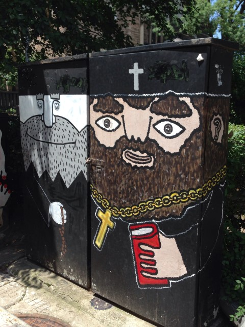 In my neighborhood, there were lots of utility boxes painted with characters and scenes. This is just outside a church.