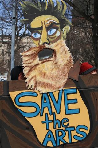 Photo by Ann Dean. For those of you not in Kansas, this cardboard cutout is a take on the mural of John Brown in the Kansas Capitol painted by John Steuart Curry. It was seen at a demonstration for arts funding in 2011, when our governor defunded the Kansas Arts Commission.