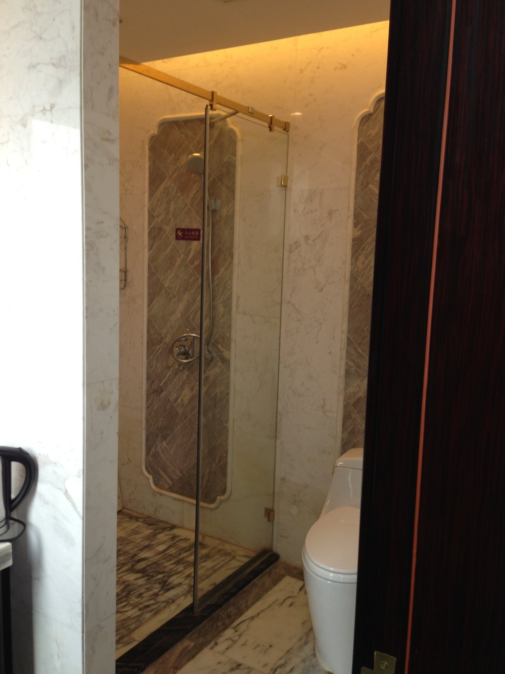 Marble-lined shower with glass doors.