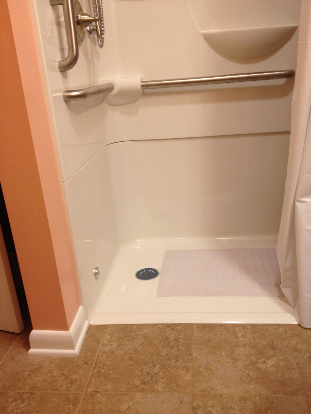 Bathroom with a handicap shower and a threshold that is less then an inch high