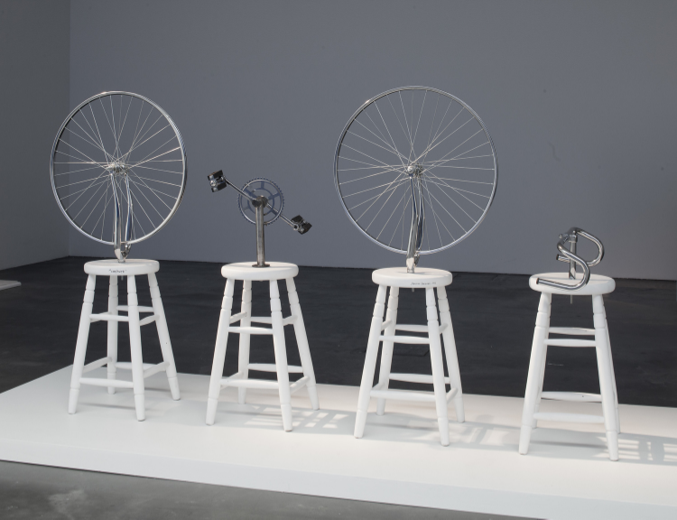 2002 Bicycle parts, stools and paint 68 x 80 x 16 in   (172,7 x 203,2 x 40,6cm) Complete is a sculpture in honnor of renowned French artist Marcel Duchamp, whose work is associated with the Dadaist and Surrealist movements. Duchamp is considered on of the most important artists of the twentieth century and has always been an important influence for Sebastian Errazuriz. Complete is both an homage and a mischievous job at Duchamp's famous readymade sculpture, named « Bicycle Wheel », which depicts a single wheel on top of a stool. Errazuriz, in his competitive nature, couldn't resist sacrilegiously indicating that his idol's work might not have been« complete », and that his own completed version is better.