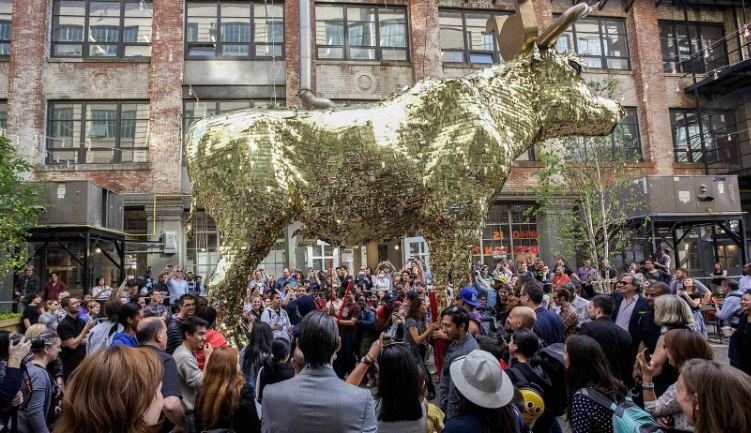 "2014 Wood, foam, metal, Mylar, Dollar bills. 15 x 24 x 5 foot (4m57 x 7m32 x 1m52) Titled ""XXTH CENTURY CAPITAL"" the giant golden piñata was not only a representation of the Gold Calf worshiped in the Bible; but also had a close resemblance to the Wall Street Bull. As if this wasn't enough, ErraZuriz proposed that instead of being filled with candy, his Giant Piñata instead be filled up through the butt with real dollar bills. ""I wanted to create a piece that could part of a celebration. Coming from South America, most kids had birthday Piñatas filled with candy. It occurred to me that it would be amazing to build a giant piñata that could be hung between buildings and invite young designers to grab some sticks and have a go at it during the party."" ""I wanted to create a simple piece that could be part of a fun celebration and yet also offer other more interesting readings. The piece hints at the Capital system as an idol that we have worshiped for decades and is unfortunately proving to be false. There's an urgent need for corrections to the Capital system that can offer a more fair redistribution of wealth. The cash cow needs to be smashed but we must be careful not to replace it with more of the same."" ErraZuriz's Giant Piñata functions as a playful warning: the masses of people that will destroy the Piñata as a symbol of capitalism will be the same who, moments later, will ironically be scrambling to fight for the money falling out. The piece like many of Sebastian's works offers several interpretations and here not only represents a criticism to the Capitalist system but also offers a quick portrait of how greed can swiftly affect us. Ultimately despite the tongue in cheek social critique, ErraZuriz warns, that his piece is a celebratory work: ""As much as I like layering and distilling concepts into simple ideas, at the end of the day, this is just one Giant Piñata that will be fun for everyone to enjoy."