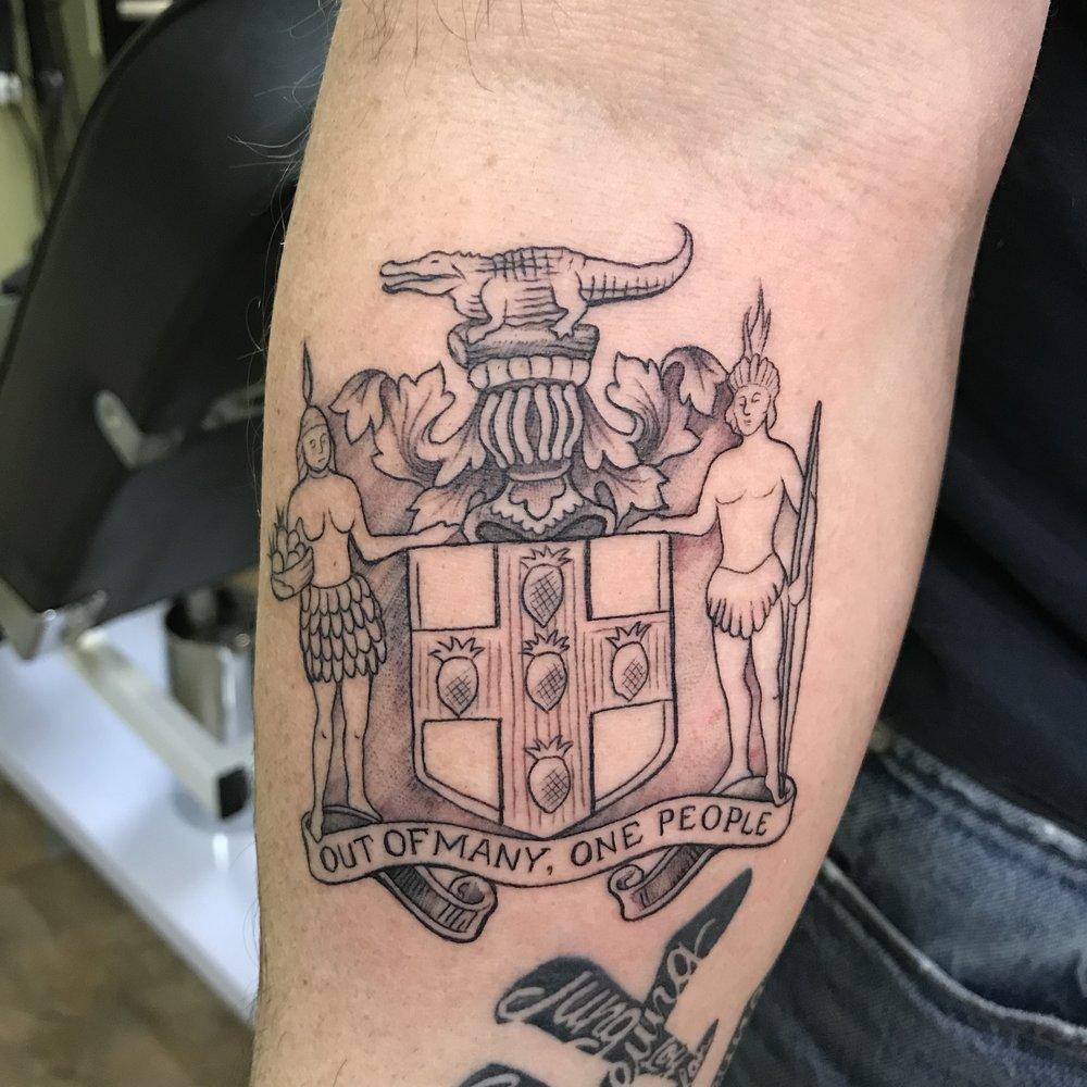 fine line single needle Justin Turkus Philadelphia best tattoo artist wong jamaica crest.jpg