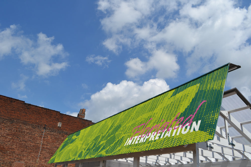 A graphic painted on reused corrugated metal advertises Floriated Interpretation Nursery