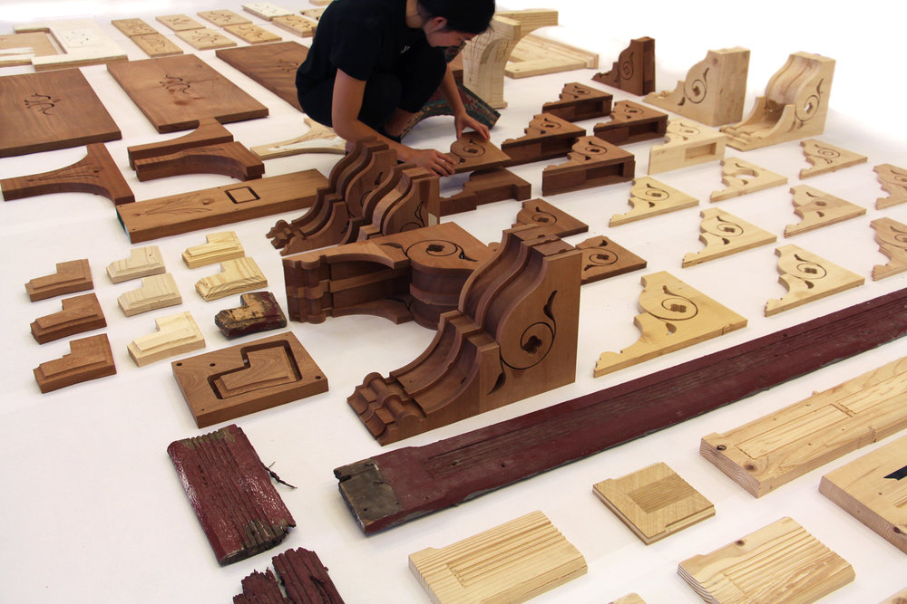Photograph of the array of Victorian elements studied, including original artifacts, CNC-milled Pine prototypes, and final Mahogany components prior to installation the building.
